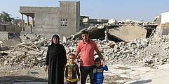 Ein Mann, eine Frau und zwei kleine Jungen stehen vor den Trümmern eines zerstörten Hauses.