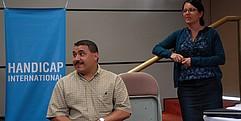 Ein Mann sitzt in einem Konferenzraum im Rollstuhl und schaut zur Seite. Neben ihm steht eine Frau.