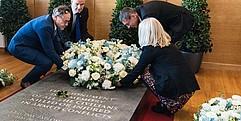 Drei Männer und eine Frau legen auf einem Grabstein mit Inschrift einen Blumenkranz nieder.