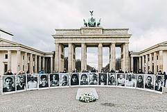 Vorne liegt das Mahnmal mit einem Kranz. Dahinter stehen Menschen in einem Halbkreis und halten sehr große Portraits hoch. Im Hintergrund das Brandenburger Tor.