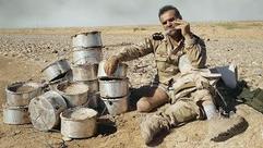 Ein Mann sitzt auf dem Boden. Er trägt Militärklamotten, sein rechtes Bein ist ein Stumpf, seine Prothese liegt auf seinem linken Bein. Vor ihm liegen mehrere metallene topfähnliche Gegenstände.