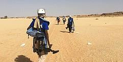 Ein Mann mit Entminungsausrüstung läuft anderen Männern hinterher.