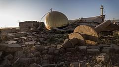 Ein Trümmerhaufen aus dem eine goldene Kuppel und die Spitze einer Moschee herausschauen.