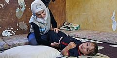 Eine Mitarbeiterin von Handicap International kniet auf dem Boden und macht Übungen mit Fayez. Dieser liegt auf dem Rücken und lacht in die Kamera.