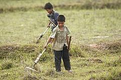 Ein Junge sucht mit einem Detektor den Boden ab