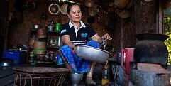Eine Frau mit Beinprothese sitzt in ihrer Hütte und arbeitet.