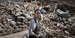 Eine Frau in Hemd und Minenschutzschürze steht inmitten von Trümmern und blickt sich besorgt nach hinten um.