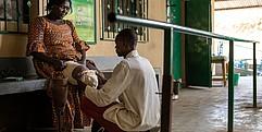 Landminen Opfer Rachel sitzt auf einer Bank. Ein Mann kniet vor ihr und passt ihre eine Prothese an.