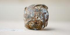 Sie Submunition ist ein runder metallischer Ball, schmutzig und rostig.