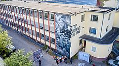 Auf dem Graffiti ist eine Familie zu sehen, die Angst vor Bomben hat. Im Himmel fliegt ein Bomber. Daneben steht der hashtag Stop Bombing Civilians.