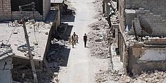 Sicht von oben auf eine zerstörte Straße. Ein paar Kinder gehen die Straße entlang.