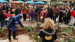 Eine Frau mit Locken steht mit dem Rücken zur Kamera. Sie scheint in ein Mikrofon zu reden. Vor ihr ist ein künstliches Minenfeld mit viele Sträuchern, etwa 8m2 groß. Ein Mann kniet gerade am Boden. Im Hintergrund stehen viele Menschen und schauen zu. Noch weiter im Hintergrund ist geschäftiges Treiben in einer Fußgängerzone zu sehen.