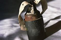 Ein kegelförmiger Metallgegenstand an dessen Kopf ein Textilband eine Schlaufe bildet.