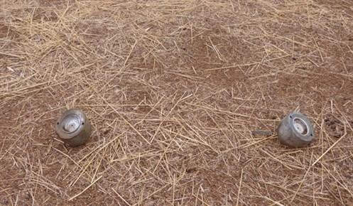 Zwei Teile Submunition liegen auf dem Boden verstreut
